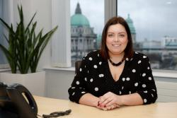 Minister Hargey pictured at her desk within Causeway Exchange