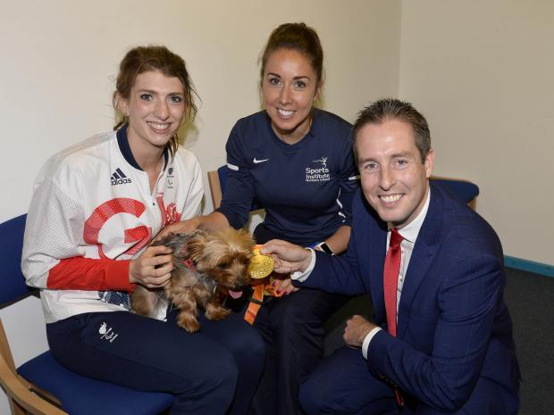 Sports Minister Paul Givan, MLA has welcoms swimmer Bethany Firth back to Northern Ireland after her historic performance in Rio. Bethany is pictured with her Yorkshire Terrier, Russell and Orla O'Rourke from Sports Institute.