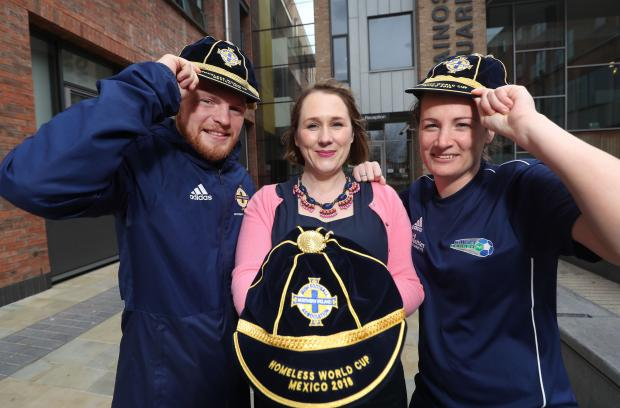 Moira Doherty and two members of the Northern Ireland homeless world cup squad show off caps presented to each member of the squad
