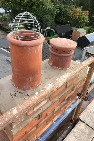 On the left is a wire cowl to discourage nesting birds in summertime, set in a terracotta pot, serving a flue in use. To the right is a 'mushroom' cowl on a terracotta Victorian chimney pot, serving a flue which is no longer in use.